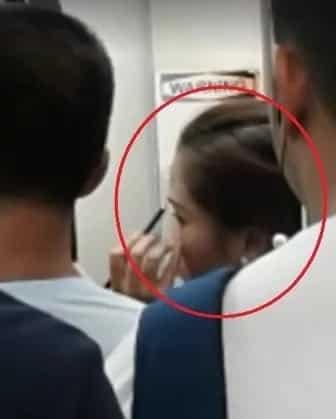 Woman puts make-up while travelling through LRT