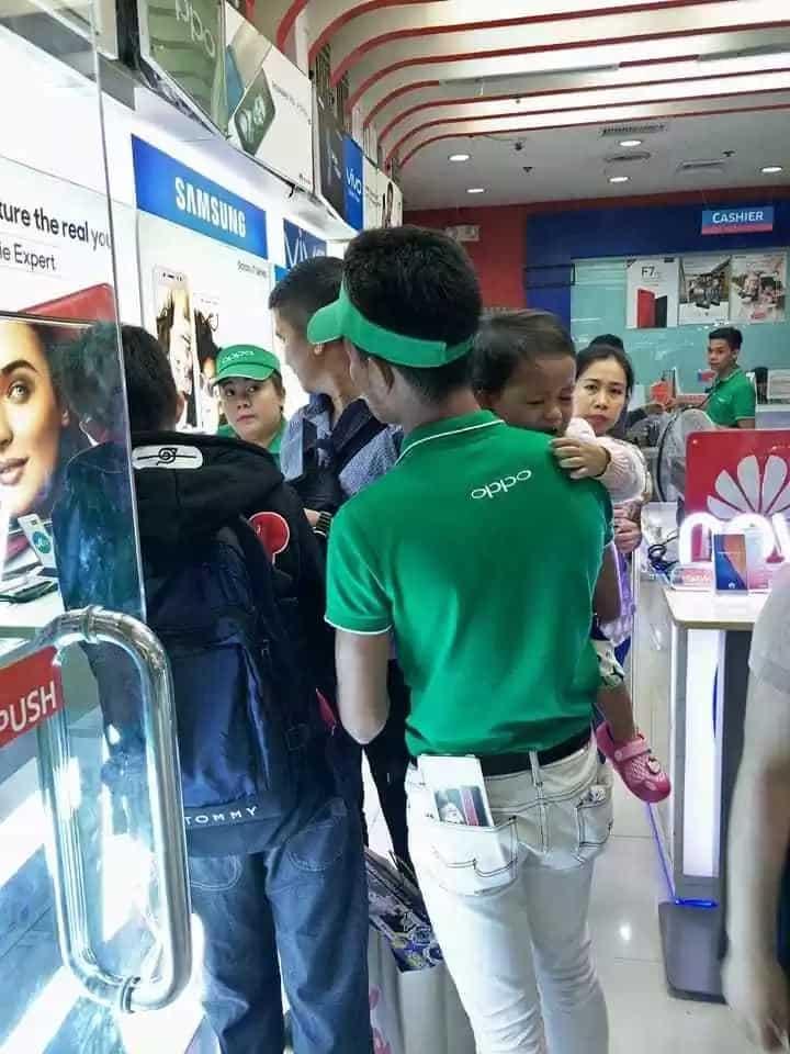 Mobile phone sales agent karga-karga ang anak habang nagtatrabaho