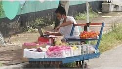 Fruit vendor na naka-laptop habang naglalako, dumadalo pala ng kanyang online classes