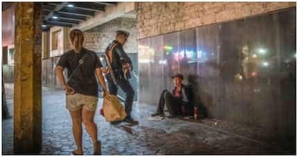 Larawan ng 1 gwardiya habang tinutugtugan ng gitara ang 1 pulubi, viral