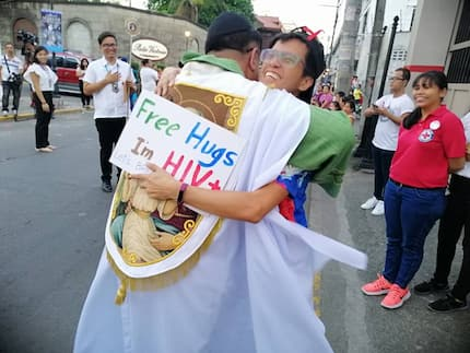 Break the stigma! HIV positive person gets a warm hug from a priest