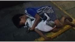 Larawan ng bata at alagang aso nito na magkayakap sa kalye, viral